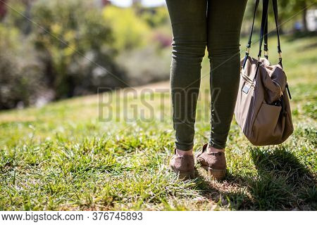 Woman Feet On Green Grass Holding A Bag With Copy Space