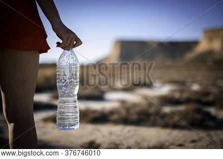 Unrecognizable Woman Holding Unlabeled Plastic Water Bottle On Arid Soil Into Desertic Landscape