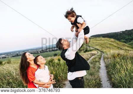 Family Of Four Outdoors In The Countryside. Young Parents And Their Two Sons - Toddler And School Ag