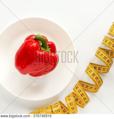 Still Life Consists Of Sweet Pepper, A Plate And A Centimeter. White Background. Diet Helps You Lose