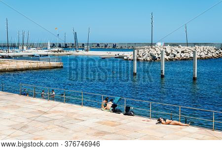 BARCELONA, SPAIN - JUNE, 24 2020: People sunbathing and swimming in the ocean at the Parc del Forum public park in Barcelona, Spain