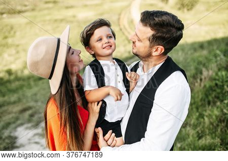 Cheerful Family Shot On A Field. Loving And Caring Young Parents Are Holding Their Little Kid On The