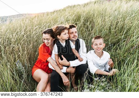 Family Of Four Sits In A Meadow In Tall Grass. Young Parents And Their Two Sons - Toddler And School