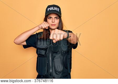 Young beautiful brunette policewoman wearing police uniform bulletproof and cap Punching fist to fight, aggressive and angry attack, threat and violence