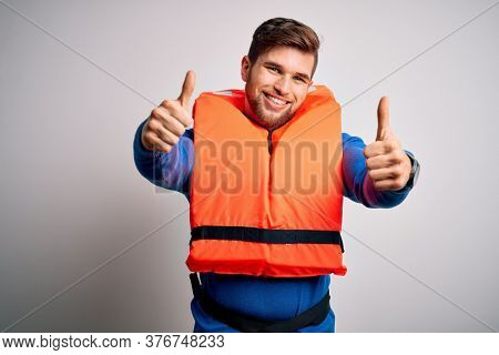 Young blond tourist man with beard and blue eyes wearing lifejacket over white background approving doing positive gesture with hand, thumbs up smiling and happy for success. Winner gesture.