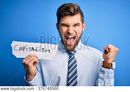 Young blond businessman with beard and blue eyes holding paper with capitalism message screaming proud and celebrating victory and success very excited, cheering emotion