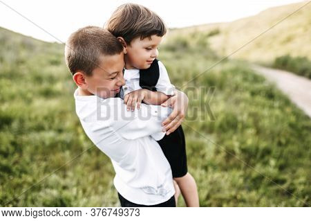 Midshot Of Two Brothers On Field Hugging. Older Brother Holds A Little One, Both Of Them Are Smiling