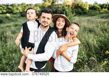 Midshot Of A Happy Family Outside On Nature. A Capture Of A Happy Family Of A Dad And Mom And Two Th