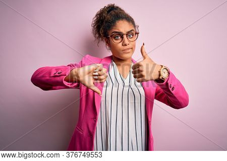 Beautiful african american businesswoman wearing jacket and glasses over pink background Doing thumbs up and down, disagreement and agreement expression. Crazy conflict