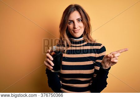 Young beautiful brunette woman drinking glass with cola refreshment using straw very happy pointing with hand and finger to the side