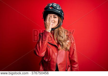 Young beautiful brunette motrocyclist woman wearing moto helmet over red background covering one eye with hand, confident smile on face and surprise emotion.