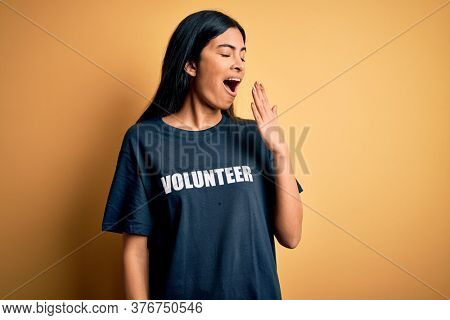 Young beautiful hispanic woman wearing volunteer t-shirt as social charity moral bored yawning tired covering mouth with hand. Restless and sleepiness.