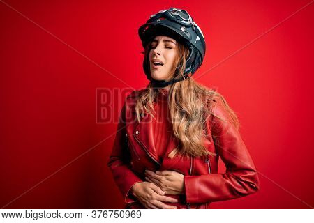 Young beautiful brunette motrocyclist woman wearing moto helmet over red background with hand on stomach because nausea, painful disease feeling unwell. Ache concept.