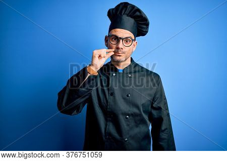 Young handsome chef man wearing cooker uniform and hat over isolated blue background mouth and lips shut as zip with fingers. Secret and silent, taboo talking