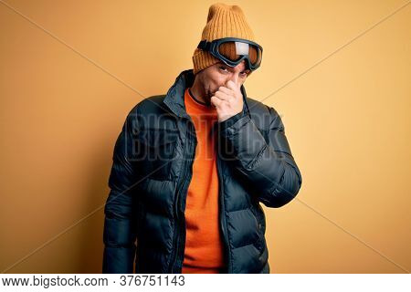 Young handsome skier man skiing wearing snow sportswear using ski goggles smelling something stinky and disgusting, intolerable smell, holding breath with fingers on nose. Bad smell