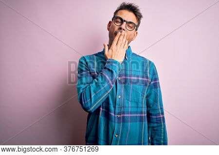 Young handsome man wearing casual shirt and glasses standing over isolated pink background bored yawning tired covering mouth with hand. Restless and sleepiness.