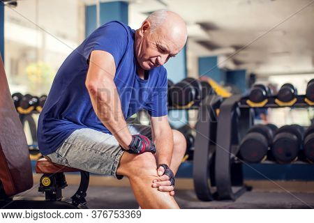 A Portrait Of Bald Senior Man Feeling Strong Knee Pain During Training In The Gym. People, Healthcar