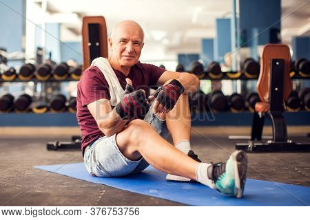 A Portrait Of Bald Senior Man In The Gym Training In The Cardio Zone. People, Health And Lifestyle C