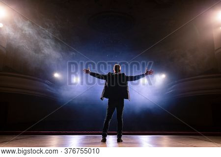 Showman. Middle Age Male Entertainer, Presenter Or Actor On Stage. Arms To Sides, Smoke On Backgroun