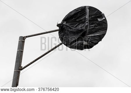 Hidden Road Sign On A Metal Pole Covered With Black Plastic Is Under Overcast Gray Sky