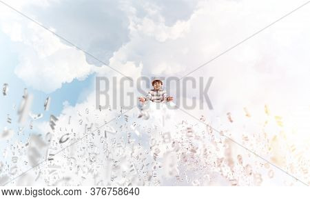 Young Little Boy Keeping Eyes Closed And Looking Concentrated While Meditating Among Flying Letters