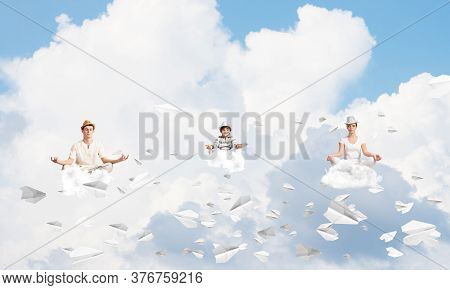 Young Family Keeping Eyes Closed And Looking Concentrated While Meditating Among Flying Paper Planes