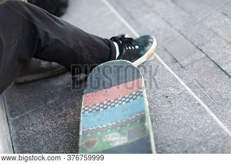 Young Boy Skater Sitting With Skateboard At City