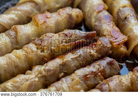 Fried Sausages In Bacon. Bacon Roll Closeup. Abstract Background With Bacon.