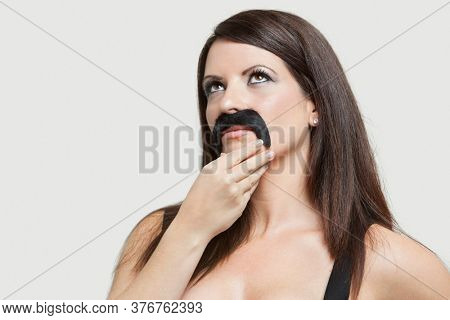 Contemplative young woman with a fake mustache looking up over gray background