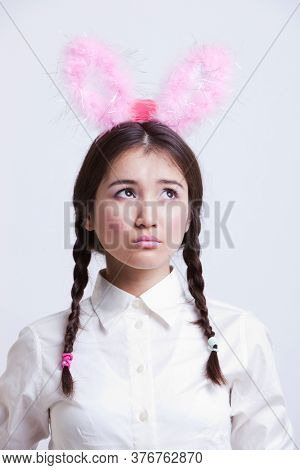 Contemplative Asian woman with bunny ears against white background
