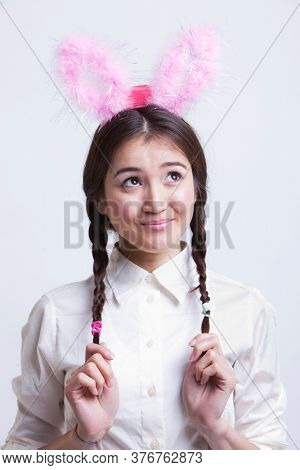 Young Asian woman with bunny ears daydreaming against white background