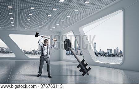 Determined Businessman In Modern Interior Breaking With Hammer Stone Key Figure