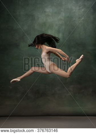 Target, Achievement. Graceful Classic Ballerina Dancing On Dark Studio Background. Pastel Bodysuit.