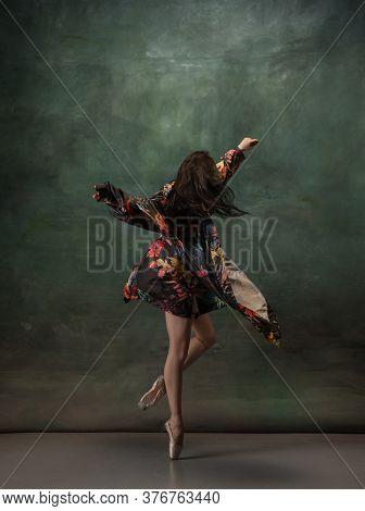 Fashionable. Graceful Classic Ballerina Dancing On Dark Studio Background. Bright Coat. The Grace, A