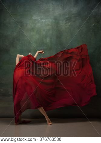 Passioned In Motion. Graceful Classic Ballerina Dancing On Dark Studio Background. Deep Red Cloth. T