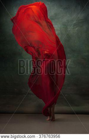Love Emotion. Graceful Classic Ballerina Dancing On Dark Studio Background. Deep Red Cloth. The Grac