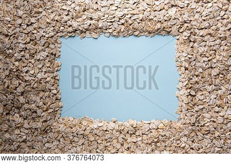 Background With Natural Dry Rolled Oats, Square Copy Space Frame And With Blue Paper Texture In It.