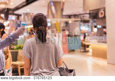 Security Guard Checking Woman Temperature At Shopping Mall Entrance.