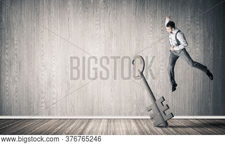 Determined Businessman In Empty Interior Breaking With Fist Stone Key Figure