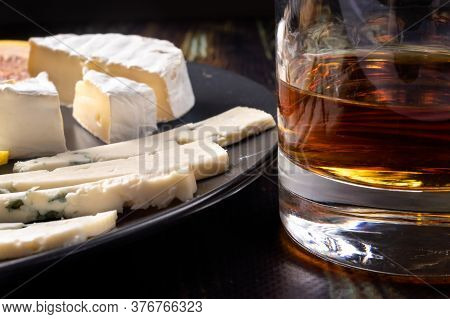 Whiskey In A Glass And An Appetizer For Whiskey Blue Cheese And Camembert Cheese. Appetizer For Alco
