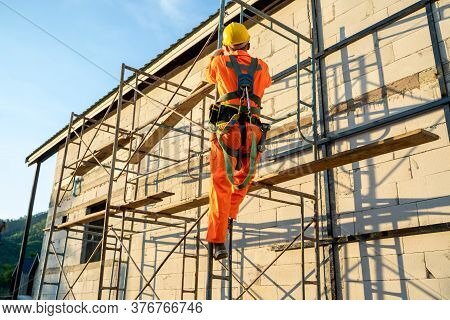 Construction Worker Wearing Safety Harness Belt During Working At High Place At Construction Site.