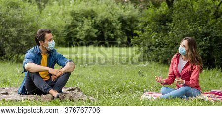 Couple have date during the coronavirus lockdown crisis. Man and woman in the park. Social distancing and virus protection.