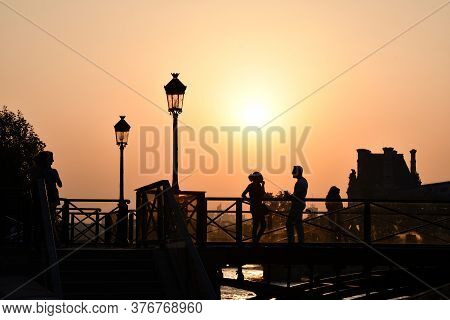 Paris / France - 06 26 2019: Silhouettes Of Unrecognizable People On Bridge Over Seine River In Fron