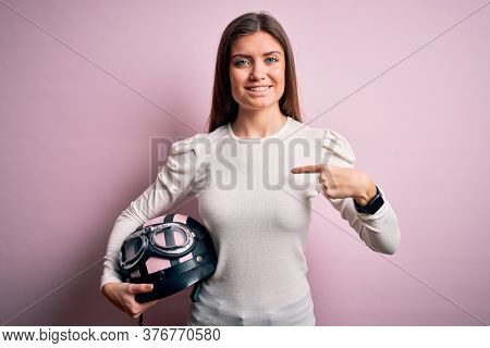 Young beautiful motorcyclist woman with blue eyes holding moto helmet over pink background with surprise face pointing finger to himself