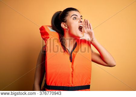 Young beautiful brunette woman wearing orange safe lifejacket over yellow background shouting and screaming loud to side with hand on mouth. Communication concept.