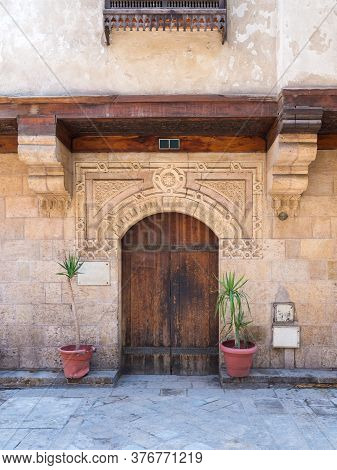 Facade Of Old Stone Bricks Decorated Wall With Arched Wooden Door