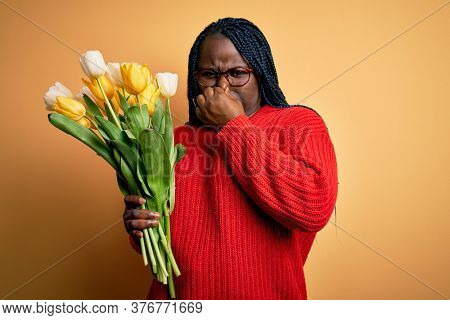 Young african american plus size woman with braids holding bouquet of yellow tulips flower smelling something stinky and disgusting, intolerable smell, holding breath with fingers on nose. Bad smell