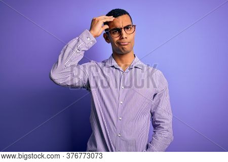 Handsome african american man wearing striped shirt and glasses over purple background worried and stressed about a problem with hand on forehead, nervous and anxious for crisis