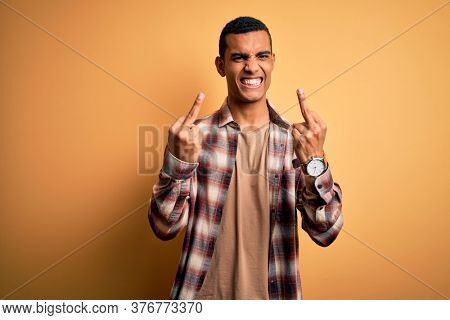 Young handsome african american man wearing casual shirt standing over yellow background Showing middle finger doing fuck you bad expression, provocation and rude attitude. Screaming excited