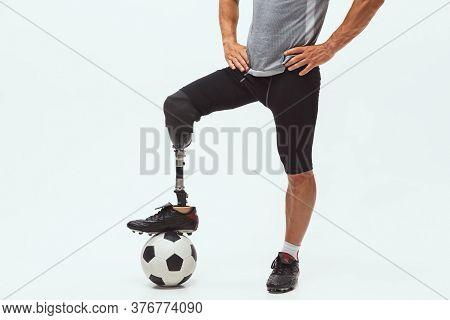 Athlete With Disabilities Or Amputee On White Studio Background. Professional Male Football Player W